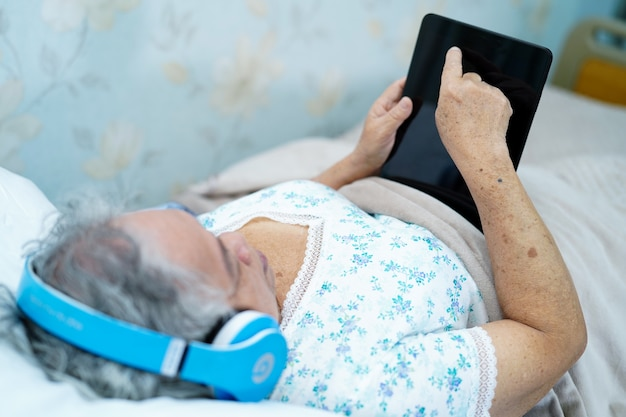Asiatischer älterer oder älterer geduldiger gebrauchskopfhörer der alten frau zur auflistung von musik