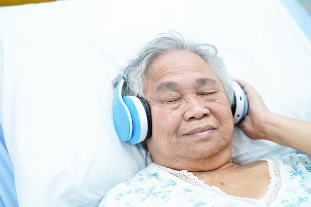Asiatischer älterer oder älterer geduldiger gebrauchskopfhörer der frau alter dame, während sich und auf bett in der krankenpflegekrankenstation glücklich hinlegen