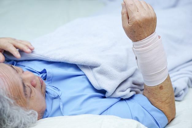 Asiatischer älterer oder älterer geduldiger schmerzfinger und -hand der alten frau in der krankenpflegekrankenstation.