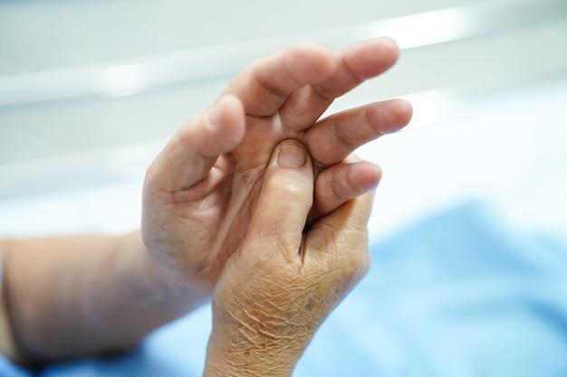 Asiatischer älterer oder älterer geduldiger schmerzfinger und -hand der alten frau.