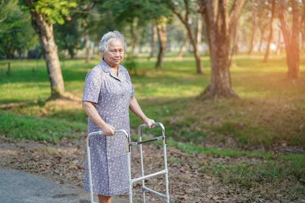 Asiatischer älterer oder älterer geduldiger weg alter dame mit wanderer im park: gesundes starkes medizinisches konzept