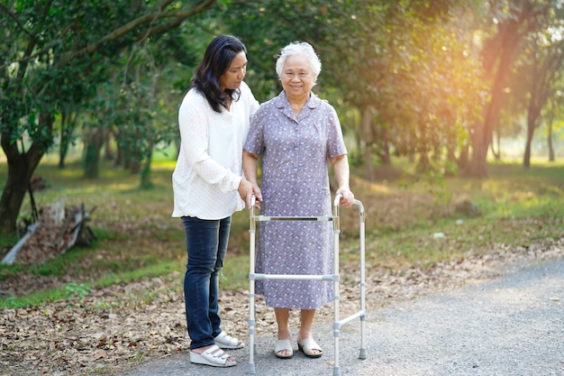 Asiatischer älterer oder älterer geduldiger weg alter dame mit wanderer im park.