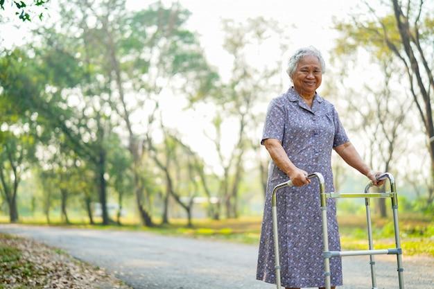 Asiatischer älterer oder älterer geduldiger weg alter dame mit wanderer im park