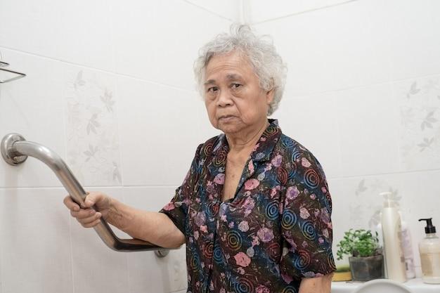 Asiatischer älterer oder älterer patient der alten dame verwendet steigungsgehweg-griffsicherheit mit hilfeunterstützungsassistent in der krankenpflegestation; gesundes starkes medizinisches konzept.