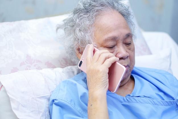 Asiatischer älterer oder älterer patient der alten damenfrau, der durch handy spricht.