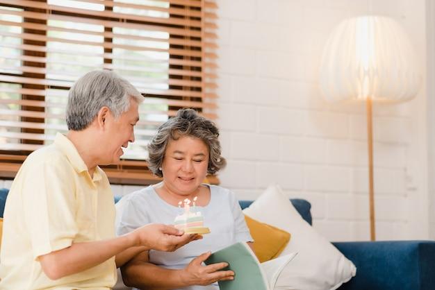 Asiatischer älterer paarmann, der den kuchen hält, der zu hause den geburtstag der frau im wohnzimmer feiert. japanische paare genießen liebesmoment zusammen zu hause.