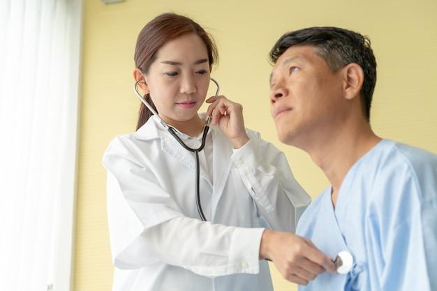 Asiatischer älterer patient auf dem krankenhausbett, das mit ärztin sich bespricht