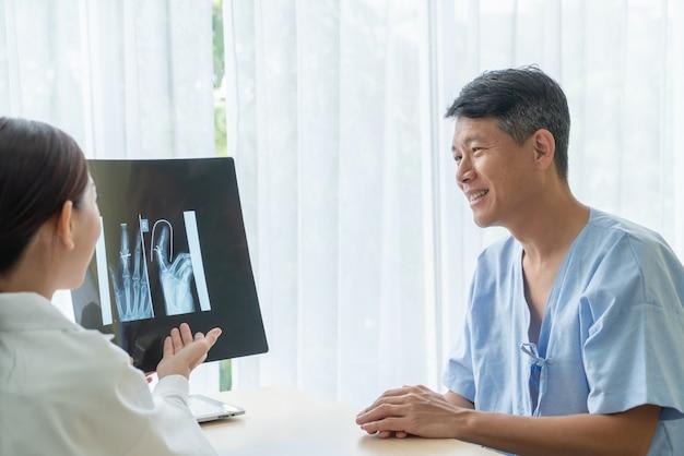 Asiatischer älterer patient, der beratung mit doktor im büro hat