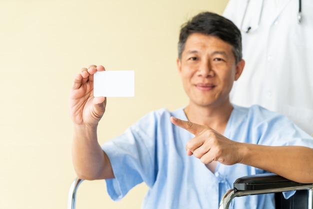 Asiatischer älterer patient im rollstuhl, der mit kreditkarte lächelt