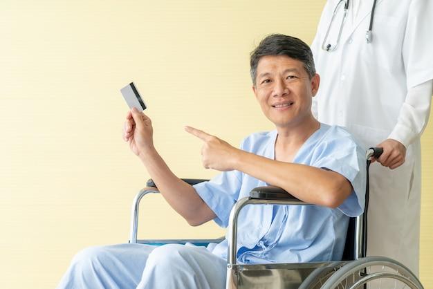Asiatischer älterer patientenrollstuhl, der mit kreditkarte lächelt