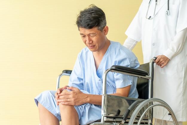 Asiatischer älterer patientenrollstuhl mit knieschmerzen
