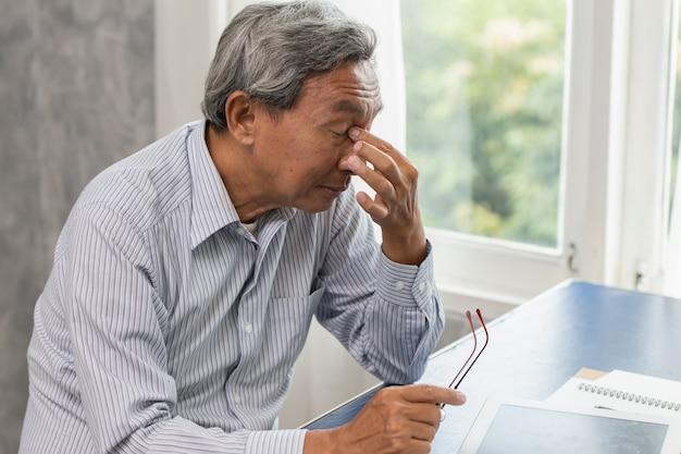 Asiatischer älterer stress, der müde ist und seine nase hält, leidet sinusschmerzmüdigkeit von der harten arbeit.
