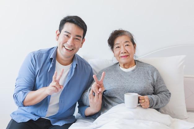 Asiatischer älterer trinkender kaffee oder tee der alten frau auf dem bett