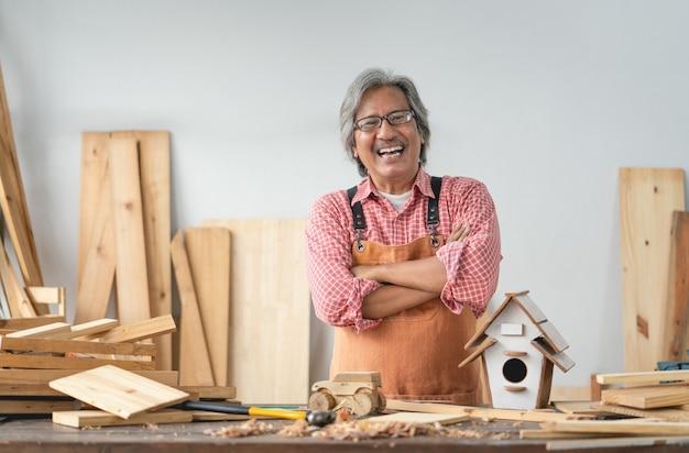 Asiatischer älterer zimmermannmann mit verschränkten armen lächeln zu hause tischlerwerkstatt