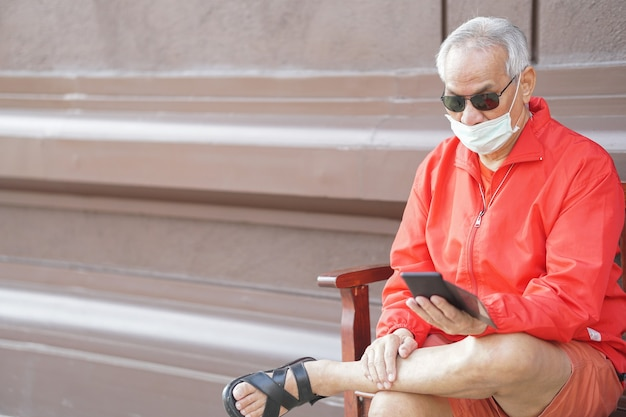 Asiatischer alter älterer älterer mann älterer mann, der gesichtsmaske unter verwendung des mobilen smartphone-handys im freien trägt