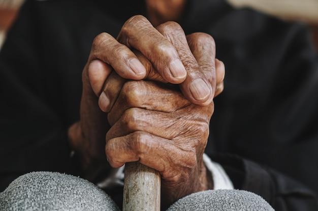 Asiatischer alter mann, der mit seinen händen auf einem gehstock sitzt