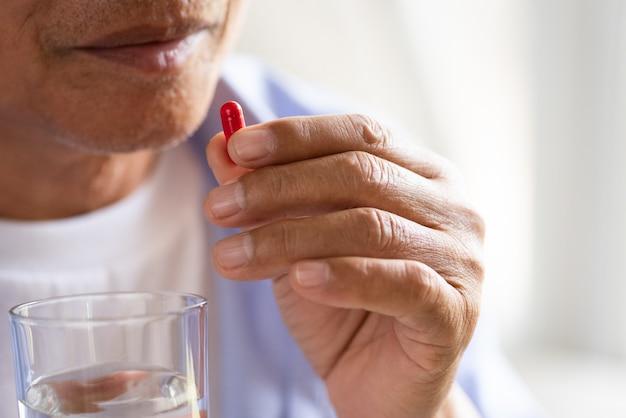 Asiatischer alter mann, der pille und eine andere hand nimmt, die ein glas hält