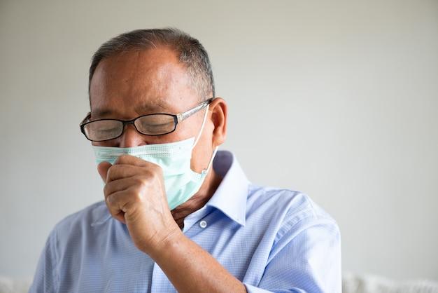 Asiatischer alter mann, der schützende gesichtsmaske und husten trägt