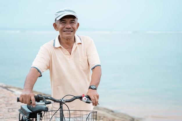 Asiatischer alter mann, der sein fahrrad am strand reitet