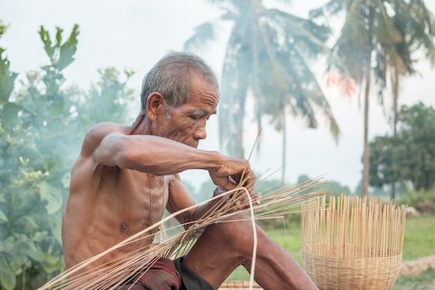 Asiatischer alter mann des onkels mit weidenwerkzeugen.