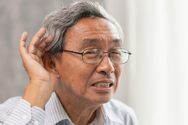 Asiatischer alter mann mit gehörlosen hörproblemen legen hand auf ohr für die hörende hilfe lauter.