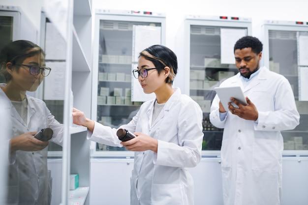 Asiatischer apotheker, der medikamente im lagerraum sortiert