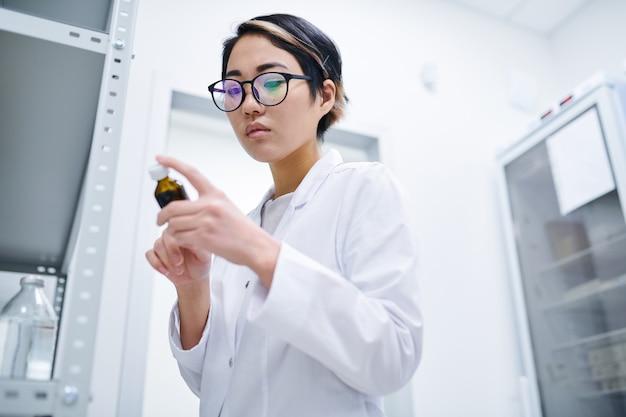 Asiatischer apotheker, der pillenetikett prüft