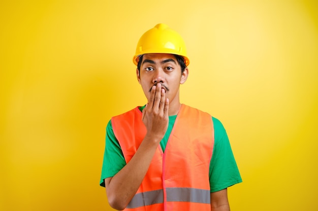 Asiatischer arbeiter, der einen helm trägt, sieht schockiert aus, als er die nachrichten hört, während er seinen mund mit den händen vor gelbem hintergrund schließt closing