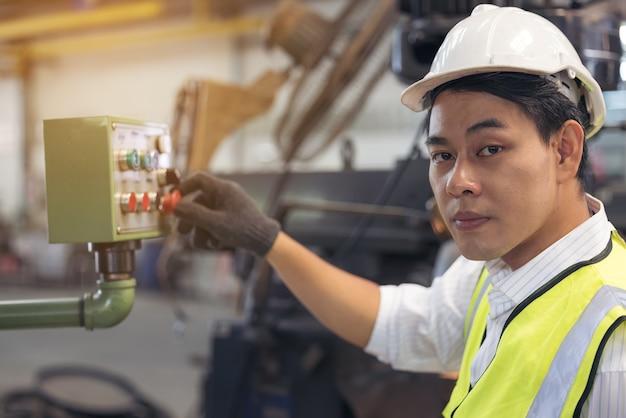 Asiatischer arbeiter, der einen helm trägt, überprüft die maschinen in einer fabrik.