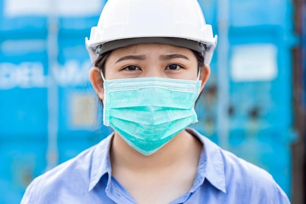 Asiatischer arbeiter trägt entsorgungsgesichtsmaske zum schutz von staubrauch und koronavirus während der arbeit am arbeitsplatz.