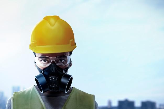 Asiatischer arbeitermann mit brille, schutzmaske und gelbem helm stehend