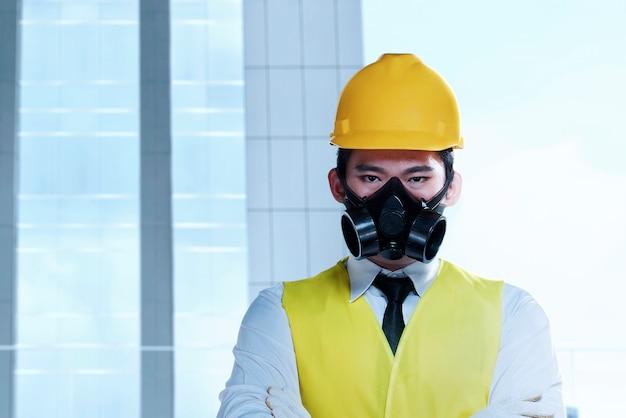 Asiatischer arbeitermann mit einer schutzmaske und gelbem helm stehend