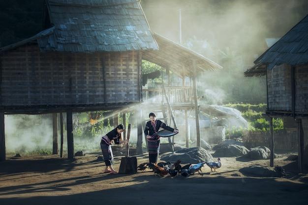 Asiatischer arbeitnehmerin, der reis getrennt zwischen reis und reishülsen und fütterungshühnern trennt