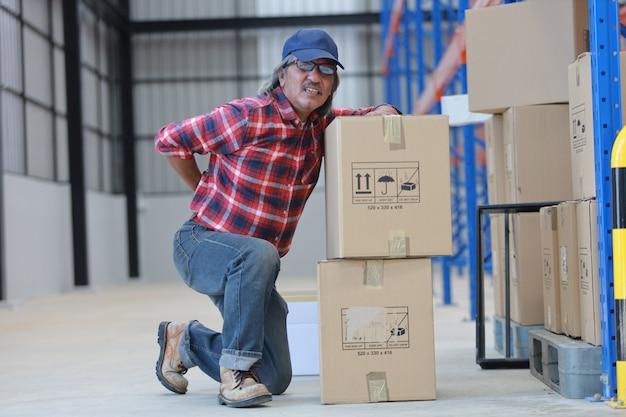Asiatischer arbeitskraftmann verletzte seinen schweren kasten des hinteren aufzugs in der fabrik