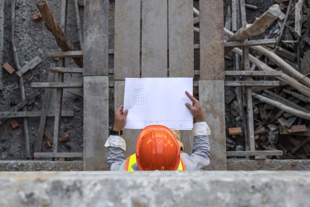 Asiatischer architekt, der projektentwurfspapiere hält und helm auf der baustelle trägt