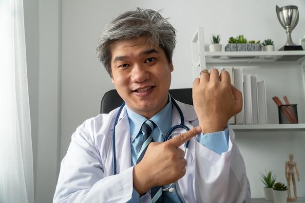 Asiatischer arzt besucht online einen patienten über die internetanwendung und notiert die symptome und erklärt, wie die ursprüngliche krankheit zu behandeln ist