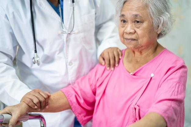 Asiatischer arzt, der asiatische ältere frau patient mit liebe berührt.