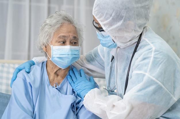 Asiatischer arzt, der gesichtsschutz und psa-anzug trägt, um den patienten zu überprüfen, der die sicherheitsinfektion schützt covid19-coronavirus-ausbruch in der quarantäne-pflegestation