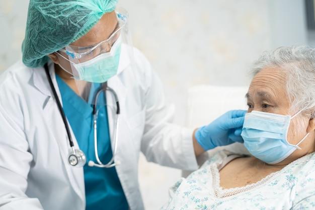 Asiatischer arzt, der gesichtsschutz und psa-anzug trägt, um den patienten zu überprüfen, um covid19 coronavirus zu schützen