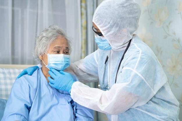 Asiatischer arzt, der gesichtsschutz und psa-anzug trägt, um zu überprüfen, ob der patient die sicherheitsinfektion covid19 schützt