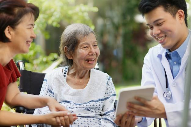 Asiatischer arzt, der mit der älteren patientin im rollstuhl spricht