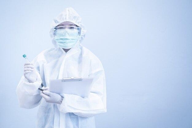 Asiatischer arzt im persönlichen schutzanzug mit reagenzglas, maske und patientenakte arbeitet hart ohne depression in der krise von covid-19.