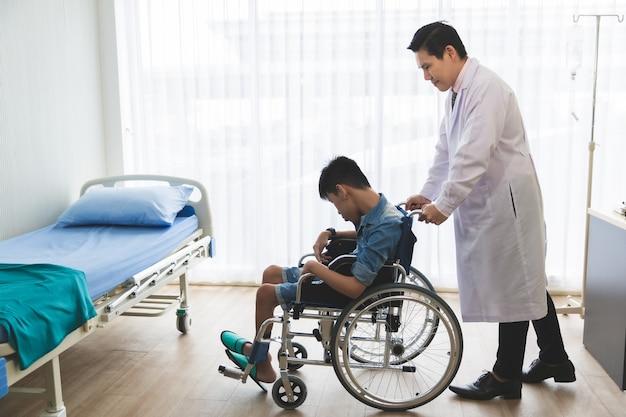 Asiatischer arzt mit behindertem jungen patienten auf rollstuhl in klinik im krankenhaus