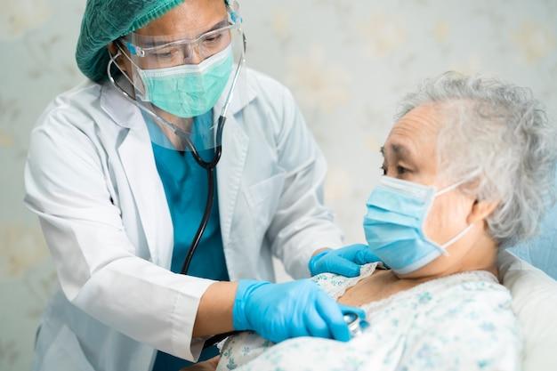 Asiatischer arzt mit gesichtsschutz und psa-anzug schützt covid-19 coronavirus.