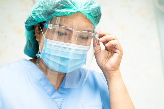 Asiatischer arzt mit gesichtsschutz und psa-anzug zur überprüfung des patientenschutzes covid-19 coronavirus.