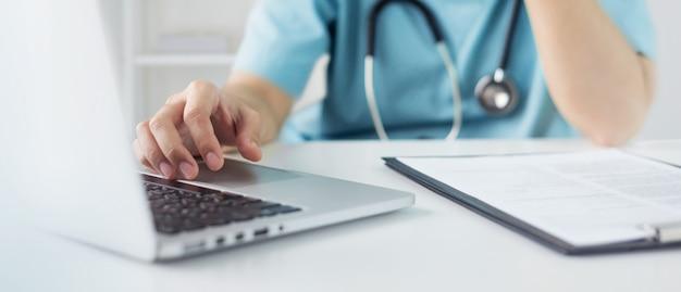 Asiatischer arzt oder krankenschwester in blauer uniform konzentrieren sich auf laptop-computer und bereiten informationen von patienten für das treffen mit dem medizinischen team im krankenhaus vor. selektiver fokus zur hand.