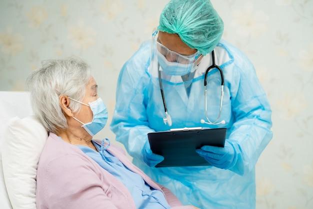 Asiatischer arzt trägt gesichtsschutz und psa-anzug neu normal, um die sicherheitsinfektion des patienten covid-19 zu überprüfen