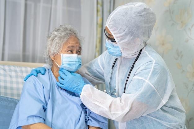 Asiatischer arzt trägt gesichtsschutz und psa-anzug neu normal, um die sicherheitsinfektion des patienten zu überprüfen. ausbruch des covid-19-coronavirus in der quarantäne-krankenstation.