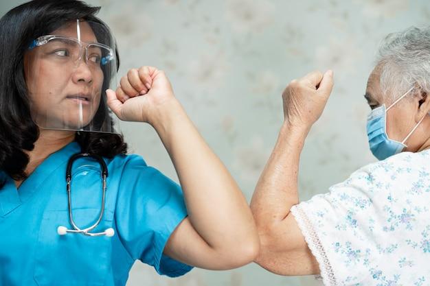 Asiatischer arzt und alter patient stoßen gegen sozial distanziertes covid-19-coronavirus