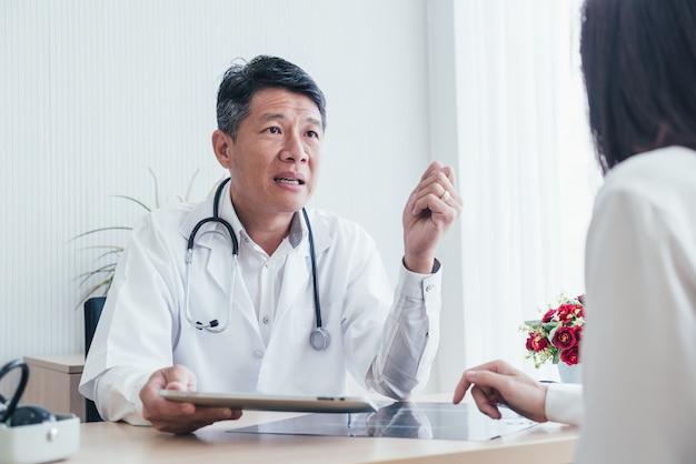 Asiatischer arzt und patient diskutieren